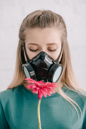Blonde woman with pollen allergy wearing respiratory mask and looking at pink gerbera flower