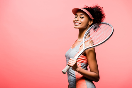Beautiful smiling African american sportswoman in sun visor holding tennis racket isolated on coral color background Stock Photo