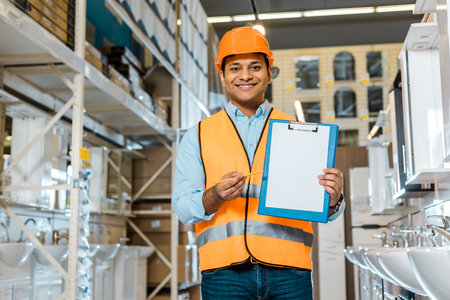 Smiling Indian warehouse worker showing clipboard with blank paper and looking at camera Archivio Fotografico