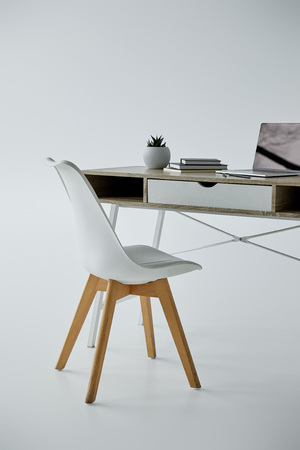 Silla blanca, mesa de oficina con ordenador portátil, libros y maceta sobre fondo gris Foto de archivo