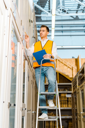 Selective focus of concentrated worker in safety vest standing on ladder in doors department