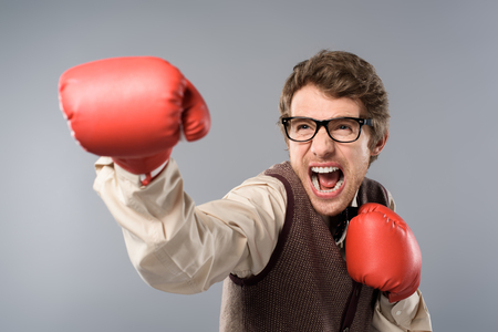 Angry man in glasses and boxing gloves screaming on grey background Stock Photo