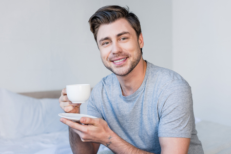 Handsome smiling man in grey t-shirt holding coffee cup and looking at camera