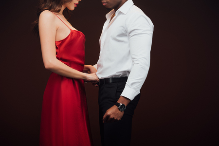 Cropped view of woman in red dress undressing African american man isolated on black background