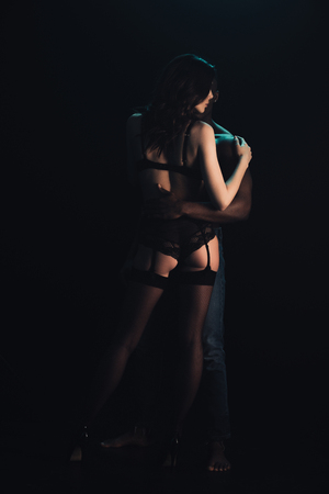 back view of african american man hugging sexy woman in lingerie and stockings isolated on black