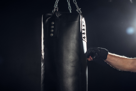 Partial view of boxer training with punching bag on black