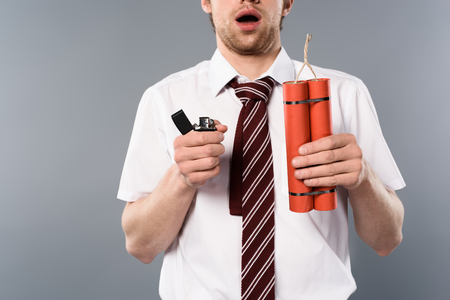 cropped view of shocked businessman holding lighter and dynamite on grey background