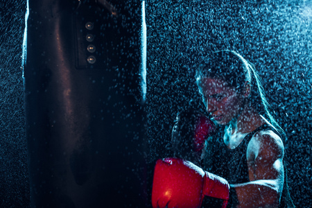 Strong boxer in red boxing gloves training under water drops on black background