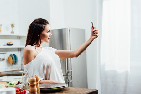 Charming young woman taking selfie near table in kitchen