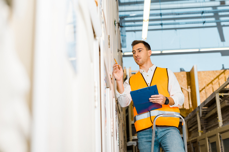Selective focus of handsome, attentive worker standing on ladder and holding clipboard Stock Photo