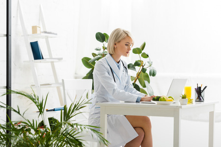 Attractive blonde nutritionist using laptop near plate with organic food
