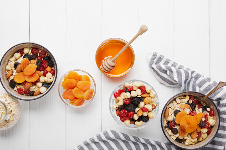 Top view of bowls with cereal, dried berries and nuts served for breakfast with dried apricots and honey near striped cloth on white wooden table