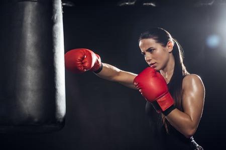 Boxeadora en guantes de boxeo rojos formación con saco de boxeo sobre fondo negro