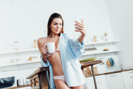 Sexy girl in white lingerie holding cup of coffee and taking selfie 写真素材