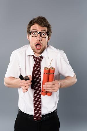 Shocked businessman in glasses holding lighter and dynamite on grey background