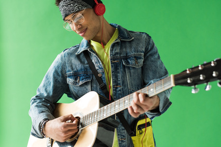 Handsome mixed race man in denim and headphones playing acoustic guitar on green screen background