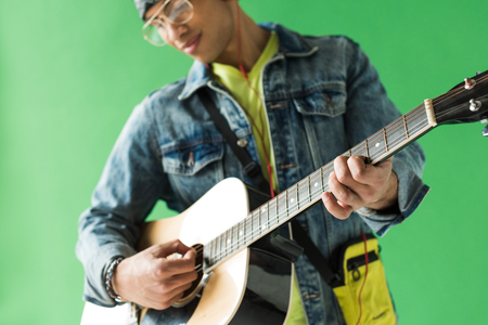 Selective focus of mixed race man in denim playing acoustic guitar on green screen background Stock Photo
