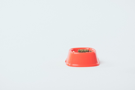 Plastic orange bowl with dry pet food on grey background with copy space
