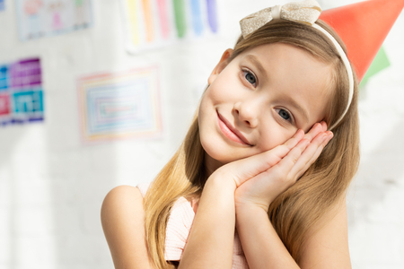 Adorable smiling kid in party cap leaning head on hands and looking at camera at home Standard-Bild