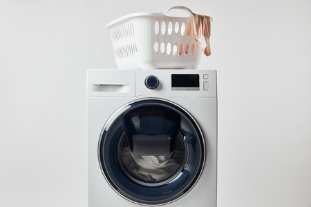 Washing machine with laundry basket isolated on grey background