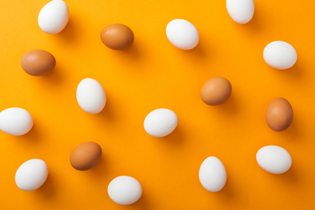 Top view of whole white and brown organic chicken eggs on bright orange background