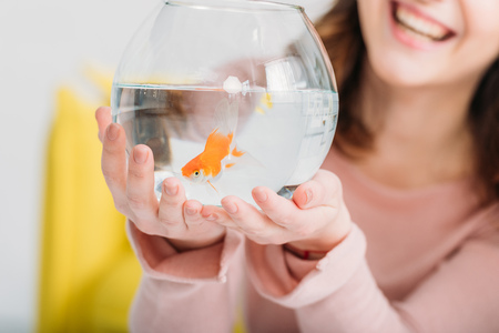 Partial view of cheerful woman holding fish bowl with bright gold fish