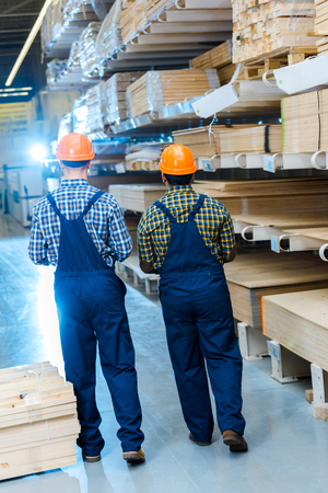 back view of two multicultural workers in overalls and helmets in warehouse