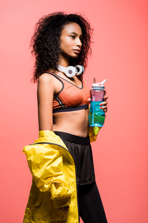 Beautiful African american sportswoman posing with headphones and sport bottle isolated on coral color background