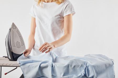 Vista recortada de chica planchando camisa azul aislado sobre fondo blanco. Foto de archivo