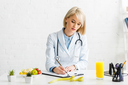 Attractive blonde nutritionist in white coat writing on clipboard Stock Photo
