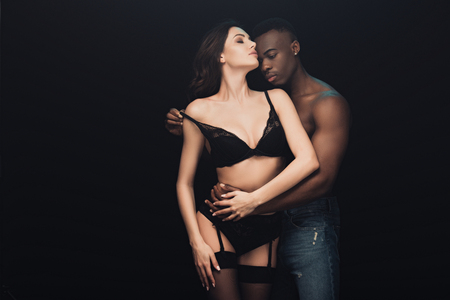 African American man undressing beautiful sexy woman isolated on black with copy space Stockfoto