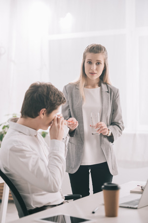 Blonde woman holding pills and glass of water near coworker sneezing in tissue
