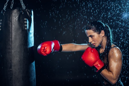 Pensive boxer in red boxing gloves training under water drops on black background