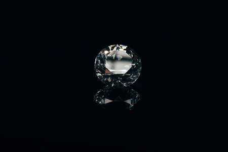 transparent pure sparkling diamond isolated on black with reflection
