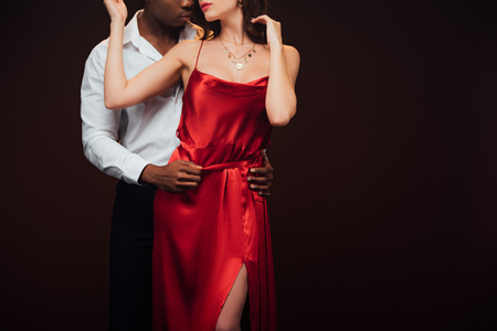 Partial view of African American man embracing woman in red dress isolated on black with copy space Standard-Bild