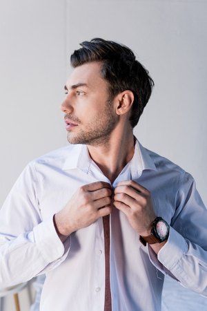 Confident handsome man putting on white shirt and looking away