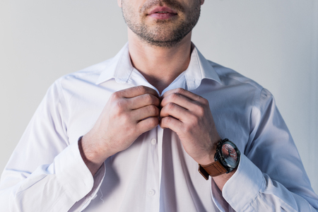 Partial view of confident handsome man putting on white shirt