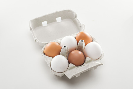 Raw white and brown chicken eggs in carton box on white background Stock Photo