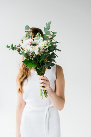 Girl in dress covering face with flowers on white background