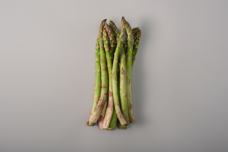 Top view of green organic raw asparagus in pile on grey background Reklamní fotografie