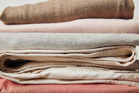 Close up view of stack of folded ironed clothes on grey background