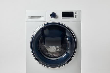 Modern washing machine with black display isolated on grey background