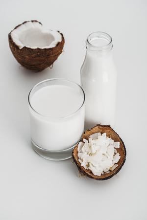 Organic vegan coconut milk near coconut half and chips on grey background