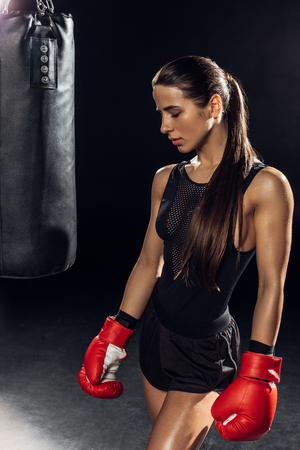 Female boxer in red boxing gloves standing near punching bag