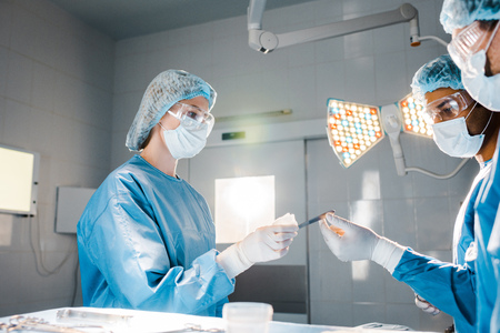 Krankenschwester in Uniform und medizinischer Kappe, die dem Arzt im Operationssaal Skalpell gibt