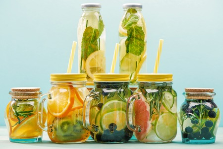 Organic detox drinks with berries, fruits and vegetables in jars and bottles with straws isolated on blue background