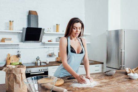 Sexy woman in underwear and blue apron kneading dough in kitchen Banco de Imagens