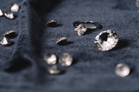 Selective focus of engagement ring near shiny diamonds on blue cloth