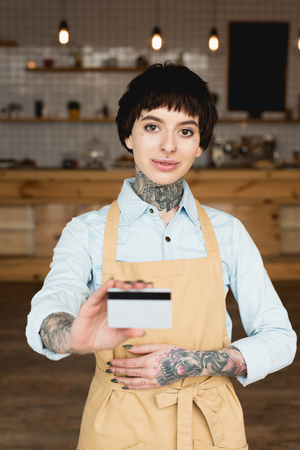 Smiling waitress proprietor in apron holding credit card and looking at camera