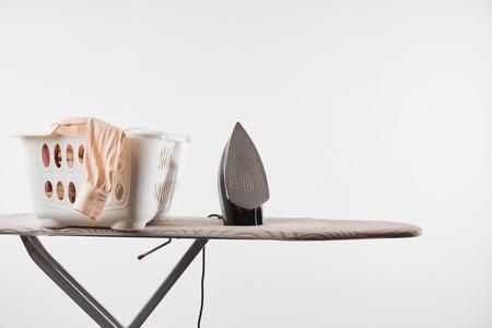 Ironing board, laundry basket and iron isolated on white background